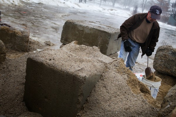 Lance Hudson scoops two buckets full of sand from the public pile in Deering Oaks Park Monday for his icy sidewalk, which only promises to get slicker as the temperature drops overnight.