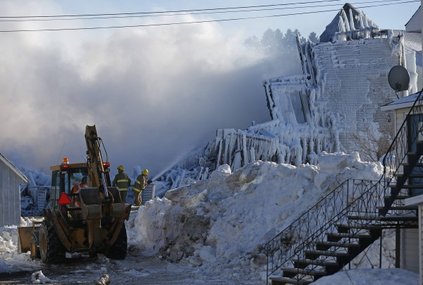 A firefighter sprays water at the Residence du Havre after a fire in L'Isle Verte, Quebec, on Thursday. Officials on Saturday feared that 32 people died in the fire.