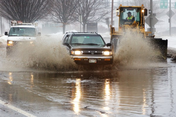 An SUV dashes through a flooded section of State Street in Portland Monday as workmen attempt to clear the storm drains.