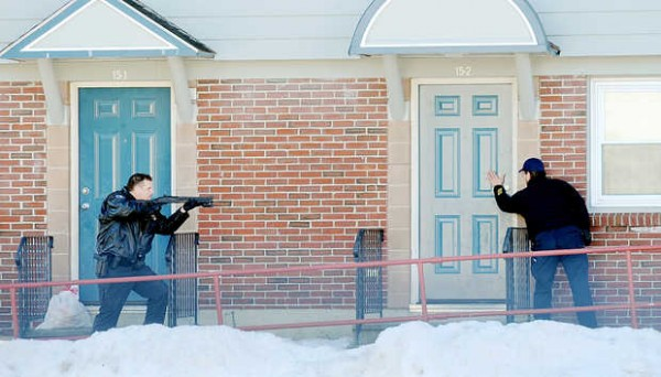 A Lewiston police officer draws his weapon as another police officer knocks on the door of an apartment on Cole Street in Lewiston on Monday morning. Officers evacuated the apartments on either side of apartment 15-2 before entering. No suspects were found in the apartment.
