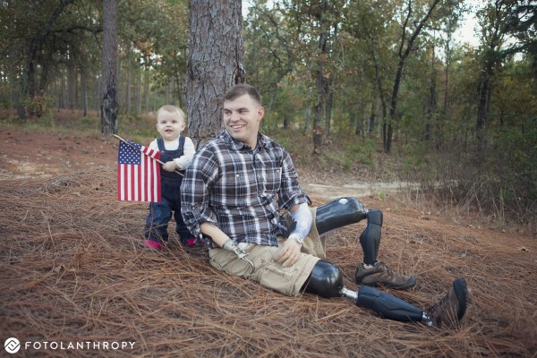 Chloe Mills holds an American flag while posing with her father, Travis Mills.