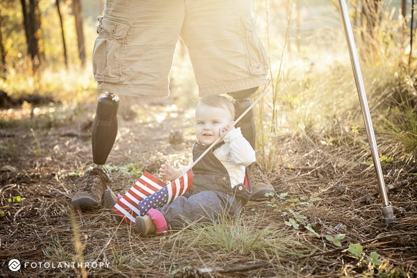 Chloe Mills holds an American flag at the feet of her father, Travis Mills.
