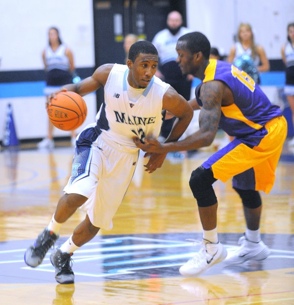 The University of Maine's Xavier Pollard (left) drives past Albany's Ede Egharevba during the men's basketball game in Orono on Saturday. The Great Danes beat the Black Bears 85-78.