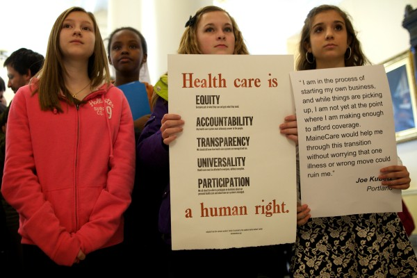 Young demonstrators hold signs at a rally and lobby day organized by the Maine Peoples Alliance at the State House in Augusta Wednesday around the issue of Medicaid expansion.