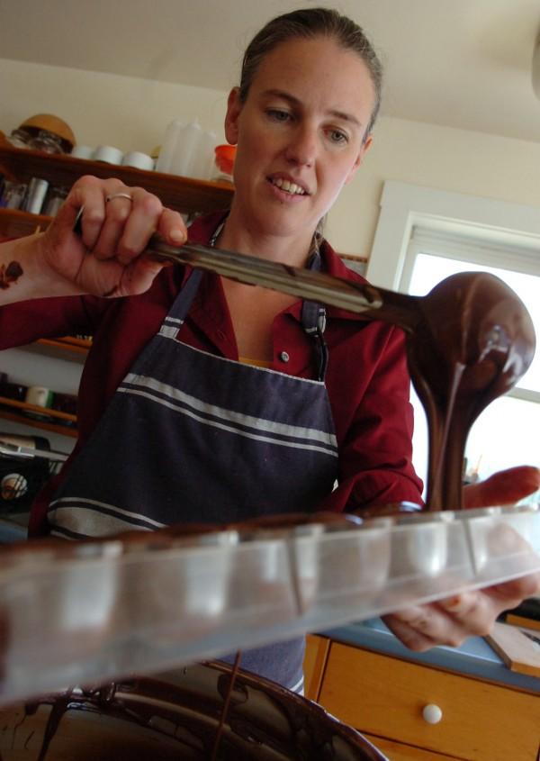 After tempering the chocolate by hand, Kate Shaffer pours the rich concoction into a mold. Shaffer, the artist behind the creations of Black Dinah Chocolatiers, makes a variety of gourmet treats at her Isle au Haut kitchen in 2007. &quotI virtually have no specalized equipment,&quot she says. &quotI love doing it by hand. I love the feeling. I don't want to lose that.&quot