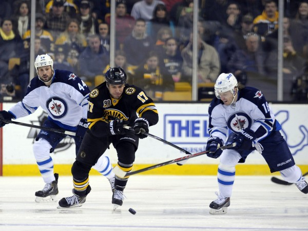 Boston Bruins left wing Milan Lucic (17) and Winnipeg Jets center Bryan Little (18) battle for a loose puck during the first period at TD Banknorth Garden in Boston Saturday.