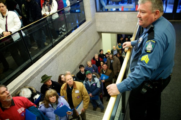 Sgt. Robert Elliot of the Capitol Police force tries to organize hundreds of people headed through security screening at the State House in Augusta Wednesday before a Maine People's Alliance rally urging legislators to make accepting federal Medicaid funds and expanding health care their top priority.