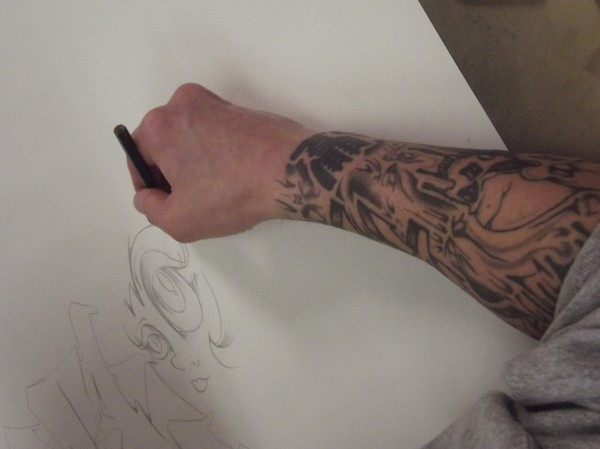 Frank Perry, his forearm covered with tattoos, works on a meticulous pencil drawing at Downeast Correctional Facility in Bucks Harbor.