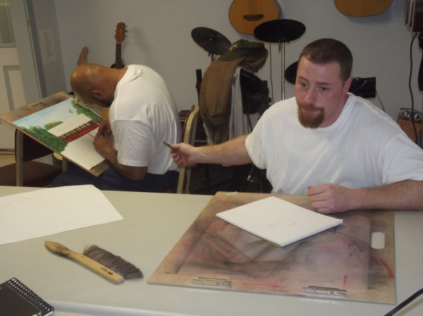 Paul Jones (right), who teaches art to other inmates at Downeast Correctional Facility in Bucks Harbor, gestures to Johnathan Smith while discussing the prison art program.