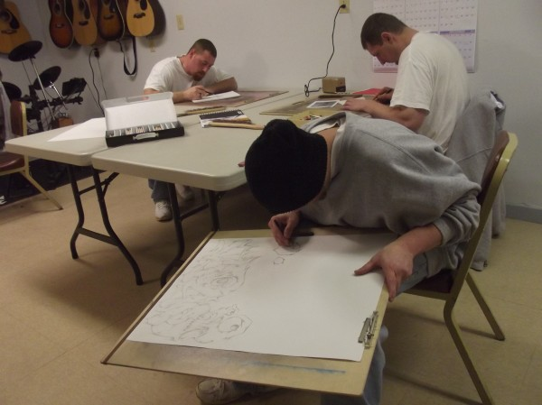 From left, Paul Jones, Frank Perry (foreground), and Glen Kleinert work on drawings at Downeast Correctional Facility in Bucks Harbor on Thursday.