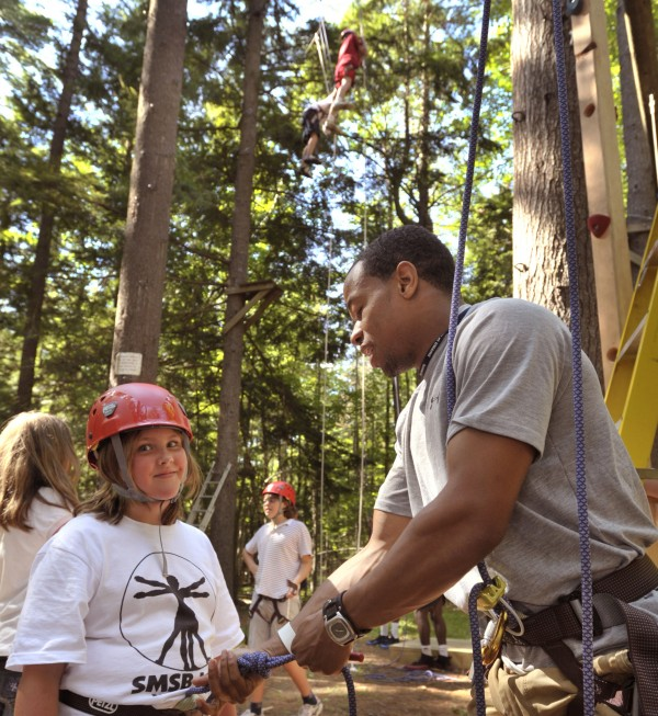 Strong Minds, Strong Bodies, Inc's. Wellness and Nutrition Summer Youth Camp director Roosevelt Boone, right, tightens the climbing harness on Rebecca Turner at the U of Maine rope climbing course Thursday, July 14, 2011.