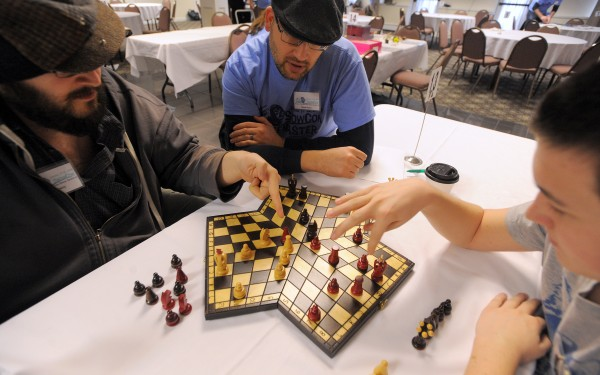 Todd Perry (left), his brother Shane Perry (center) and Adam Farrington discuss some of the rules while playing three-person chess during the sixth annual SnoCon Gaming Convention in Orono on Saturday. Shane Perry bought the game while traveling in Poland and brought it to the convention to share the experience with fellow board game enthusiasts.
