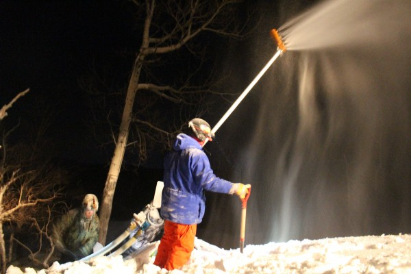 Caleb Dilworth (right), 25, of Greenbush and Aaron Obrien, 35, of Burnham clear snow away from a snow gun beside a ski trail on Sugarloaf Mountain on Jan. 9. Both are members of Sugarloaf's nighttime snowmaking crew.