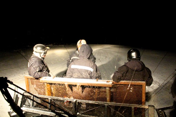 Four men from the Sugarloaf nighttime snowmaking crew pack into the bucket of a snowcat to be transported to another spot on the mountain on Jan. 9, during their 12-hour shift.