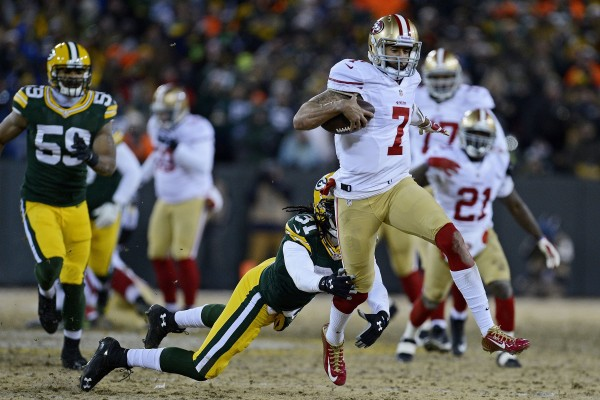 San Francisco 49ers quarterback Colin Kaepernick (7) avoids being tackled by Green Bay Packers' Davon House (31) during the second quarter of their NFC wild-card playoff game at Lambeau Field in Green Bay, Wis., on Sunday.