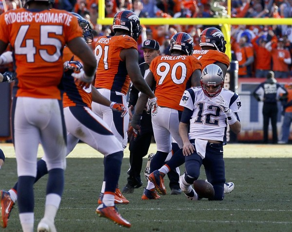 New England Patriots quarterback Tom Brady kneels on the ground after being sacked by the Denver Broncos during the fourth quarter in the NFL's AFC Championship game in Denver.