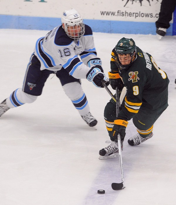 The University of Maine's Brice O'Connor (left) and Vermont's Kyle Reynolds battle for the puck during a game on Nov. 30, 2012, in Orono.