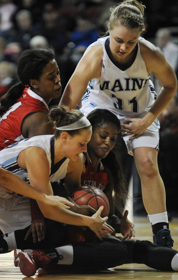 Maine's Lauren Bodine and Stony Brook's Jessica Ogunnorin wrestle for a loose ball at the Cross Insurance Center on Sunday. Standing by to help is Stony Brook's Miranda  Jenkins (top left) and Maine's Liz Wood (top right). Stony Brook won 65-49.