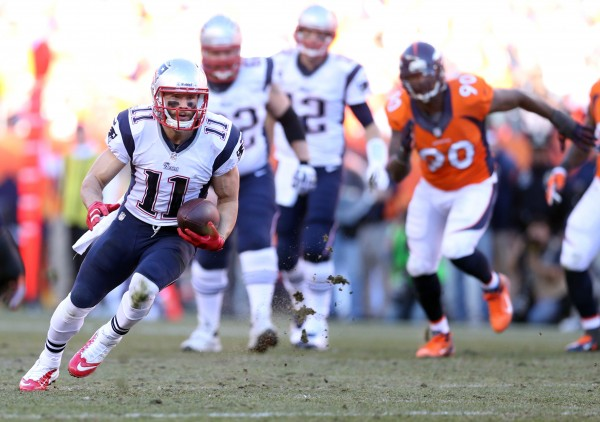 New England Patriots wide receiver Julian Edelman (11) runs the ball  against the Denver Broncos in the second half of the AFC championship Sunday at Sports Authority Field in Denver.
