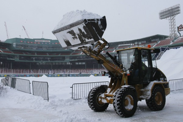 A crew clears snow in Fenway Park, home of baseball's Boston Red Sox, during a winter snowstorm January 3, 2014, in Boston, Mass. The park will be the site of the Saturday hockey match between University of Maine and Boston University.