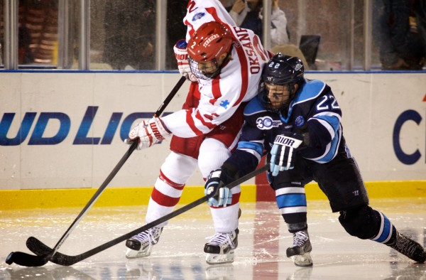 Junior Stu Higgins of the University of Maine hockey team fights for the puck with Boston University's Ahti Oksanen Saturday night at Fenway Park in Boston.
