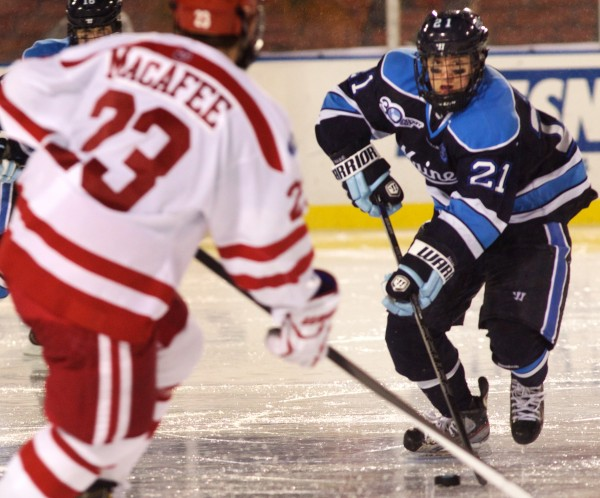Freshman Cam Brown, of the University of Maine Black Bears, skates down the ice with the puck at Frozen Fenway Saturday night in Boston. Maine beat Boston University by a score of 7-3.
