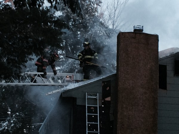 Several firefighters from the region work from the roof of a Clark Falls Road home that caught fire on New Year's Day in Orrington. Firefighters from Orrington, Brewer, Eddington, Hampden, Holden and Bucksport battled the blaze that destroyed the home of a family of five.