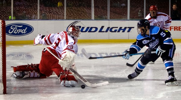 BOSTON, MASSACHUSETTS -- 01/11/14 -- University of Maine hockey's Andrew Cerretani scores a goal against Boston University Saturday in the first period at Fenway Park in Boston. Maine went on to win by a score of 7-3.