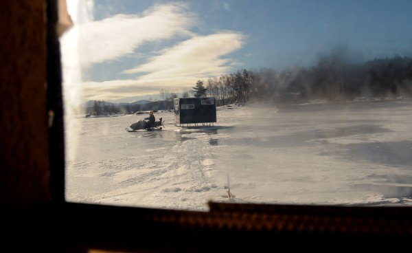A snowmobile tows an icefishing shack on the ice of Moosehead Lake in Rockwood in January 2013.
