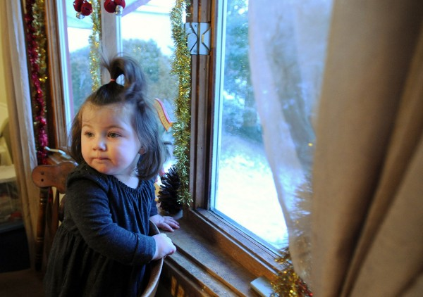 Chelsea Ouellette, 20-months-old, waits every day at the dining room window for her brother and cousins to get home from school.