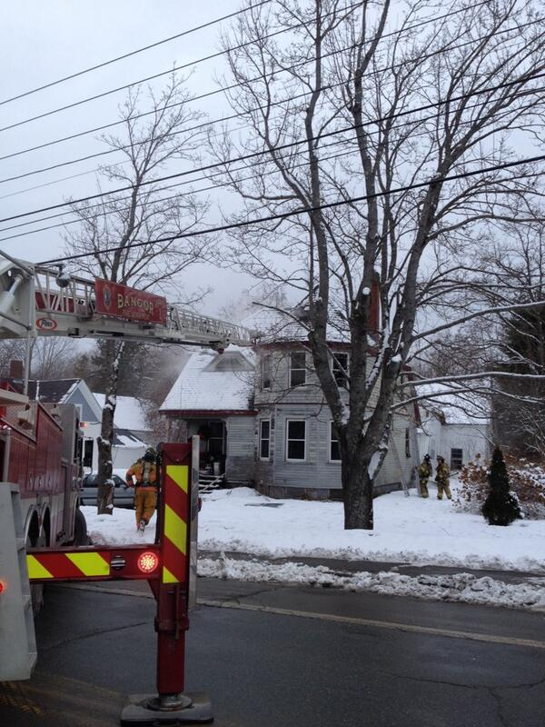Firefighters work to put out a fire at a home on Route 1A in Hampden Monday afternoon.