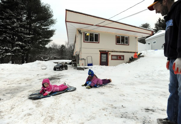 Jim Pearsall watches as his niece, Chelsea, and daughter, Haven, go sledding down the hill beside their Orono home recently.