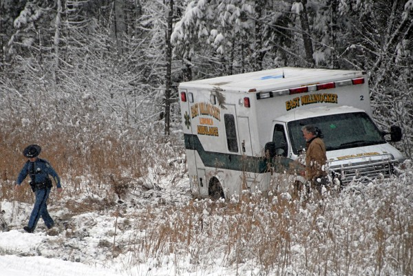 Maine State Police Trooper Trevor Snow walks away from an East Millinocket-Lincoln ambulance that rolled over while heading south on Interstate 95 in Edinburg on Monday, Dec. 2, 2013.