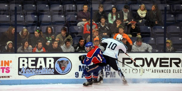 Damien Spencer of the Old Town/Orono Black Bears competes for the puck with Messalonskee's Dan Condon on Friday night at the Alfond Arena in Orono in front of a mostly Old Town student body. The Old Town/Orono varsity team is made up of 16 players from Old Town High School and six players from Orono.