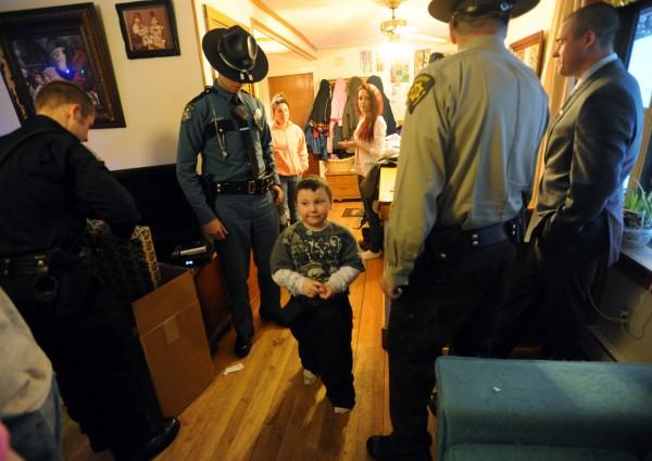Five-year-old Aidyn Ouellette walks through a group of law enforcement officials who were at his house delivering Christmas presents for him, his little sister, and their five cousins who they now reside with.