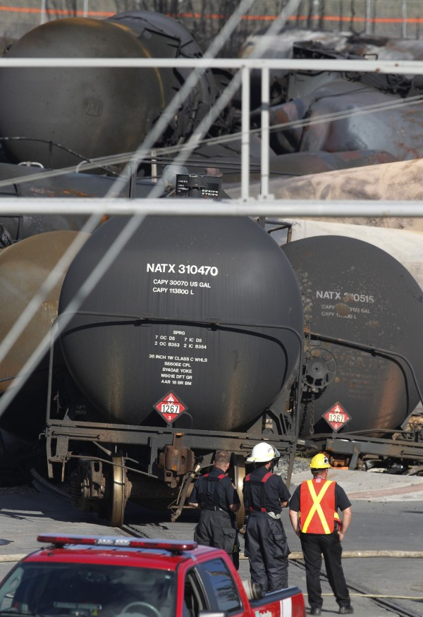 Workers look at the derailed oil cars in the downtown core in the town of Lac-Megantic, Quebec, in July 2013.