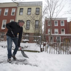New York City Mayor Bill de Blasio clears the sidewalk of snow in front of his Brooklyn home in New York on Jan. 3, 2014.