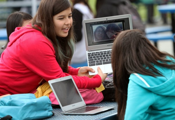 Pinacate Middle School student Melissa Lopez (left), 12, holds her Chromebook up so that Jasmin Cadenes, 12, can see it at their lunch table in Perris, Calif., recently.