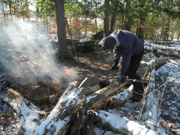 Dustin Reynolds, 17, of Unity, practices his outdoor survival skills Friday during Mount View High School's Exploratory Week. He built fires with flint and made a one-person emergency shelter of boughs, leaves and other debris. &quotI think it's really fun,&quot he said of the special week.