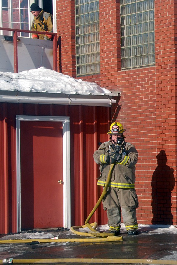Firefighter John Buckingham (right) helps collect a hose from a fire at the Katahdin Federal Credit Union on Wednesday.