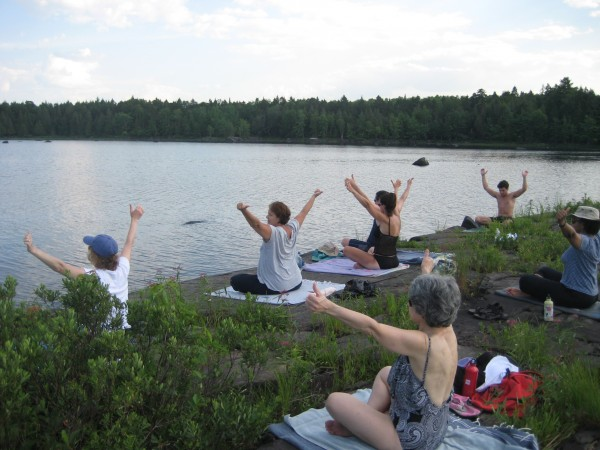 Guests of the Sewall House Yoga Retreat in Island Falls practice last year on the shore of Mattawamkeag Lake.