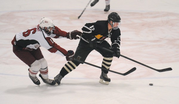 Bangor High School's Justin Courtney (left) and Maranacook/Hall-Dale/Winthrop High School's Dan Condon battle for the puck during a game last February in Bangor. Courtney has helped lead Bangor to a 5-1 start.