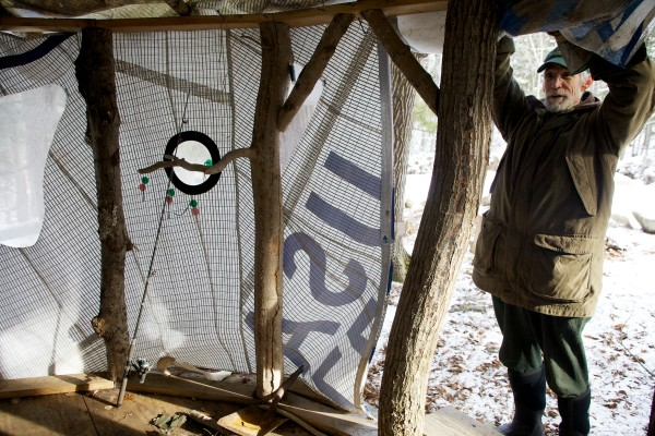 Bob Crowley, winner of the reality television series &quotSurvivor: Gabon,&quot rolls up the door flap on his original, sailcloth-draped yurt at Maine Forest Yurts in Durham.