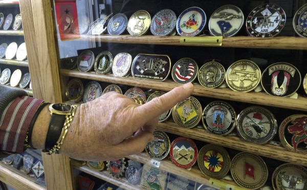 Maine Troop Greeter Chuck Knowlen, chairman of the group, points to one of 5,236 service coins that have been given to the greeters over the last 11 years at the Bangor International Airport on Tuesday.