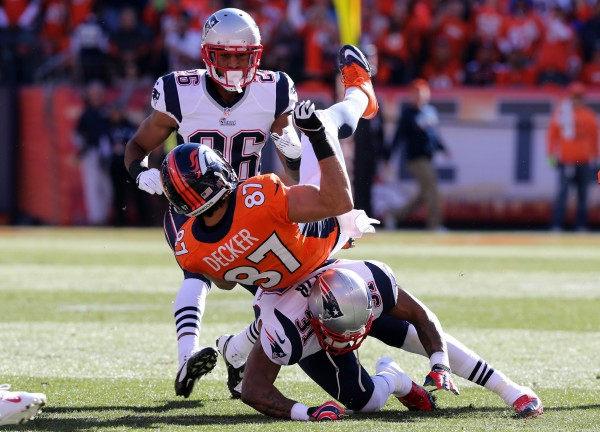 Denver Broncos wide receiver Eric Decker (87) is tackled by New England Patriots cornerback Aqib Talib (31) during the first quarter during the 2013 AFC championship playoff football game at Sports Authority Field at Mile High.