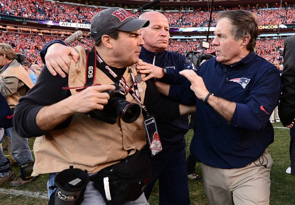 New England Patriots head coach Bill Belichick pushes photographer Damian Strohmeyer following the 26-16 loss to the Denver Broncos in the 2013 AFC Championship football game at Sports Authority Field at Mile High.