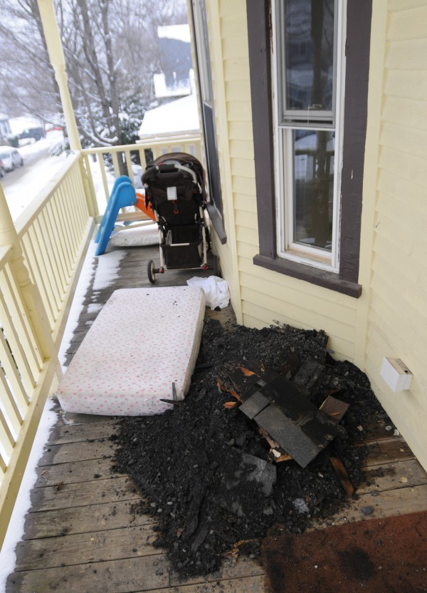Charred wood and debris litters the front porch of 40 Dillingham Street in Bangor on  Monday.