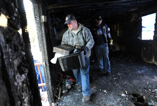 Robert Mosher (left) and Ricky Winchester carry a few found items from the Smith home Thursday afternoon while helping out their friend and home owner Roger Smith Jr. after last week's devastating fire.