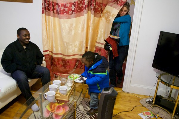 Joseph Nsabimana (left) watches his 3-year-old son Miraji help Bethany Dixon with tea and snacks at his family's apartment in Portland on Monday. Dixon was placed with the Nsabimana's through an intensive college program.