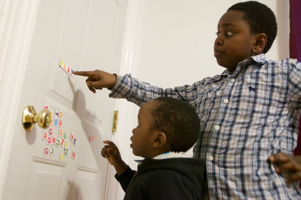 Rafiki Nsabimana, 8, asks his 3-year-old brother Miraji if the letters spell a word in the living room of their family's apartment in Portland on Monday.